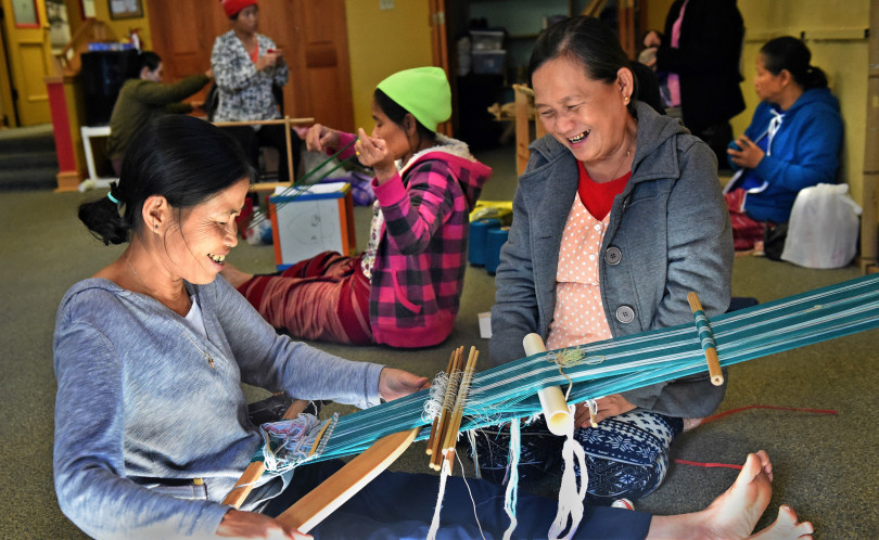Karen women, Aye Lwai (cq), left, and Rosie Say talk while Lwai weaves a bag at the East Side Freedom Library in St. Paul on Wednesday, Nov. 9, 2016. In Burma/Myanmar women and men would weave intricately patterned cloth on backstrap looms, which would be used to make sarongs, shirts and other clothing. The women are opening an exhibit of their work Friday. (Pioneer Press: Jean Pieri)